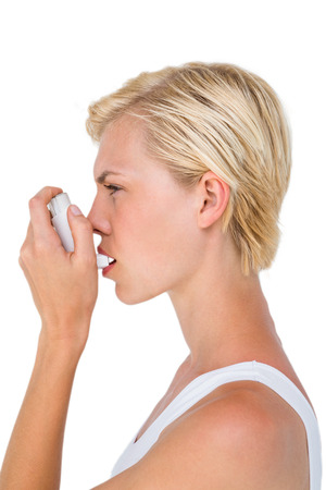 health fair: Asthmatic pretty blonde woman using inhaler on white background Stock Photo