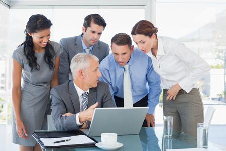 Business-Team gemeinsam auf dem Laptop im Büro Lizenzfreie Bilder