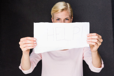 fair woman: Blonde woman showing help sign on black background