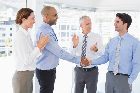 congratulating: Business team congratulating their colleague in the office Stock Photo