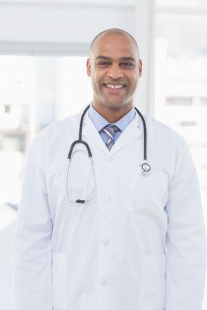 guy portrait: Confident male doctor smiling at camera in medical office
