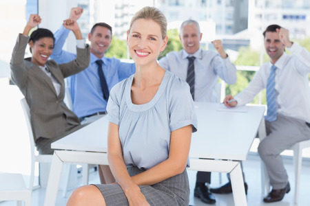 celebrate: Smiling businesswoman and her team in the office Stock Photo