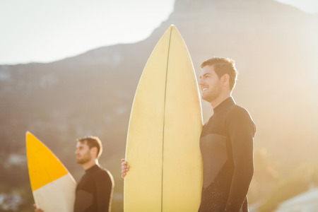 surfboard: Two men in wetsuits with a surfboard on a sunny day at the beach