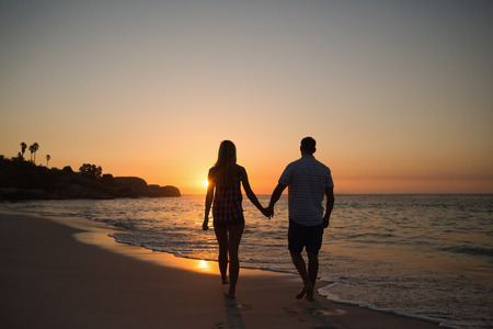 tomados de la mano: feliz pareja sonriendo a la playa