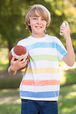 inhaler: Little boy using his inhaler on a sunny day Stock Photo