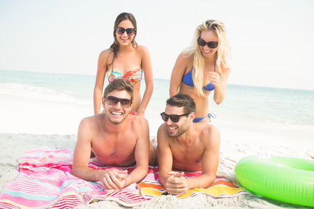handsome young athletic: group of friends in swimsuits at the beach