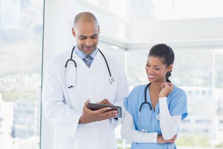 doctores: Sonriendo médicos que trabajan con la tableta juntos en la oficina médica