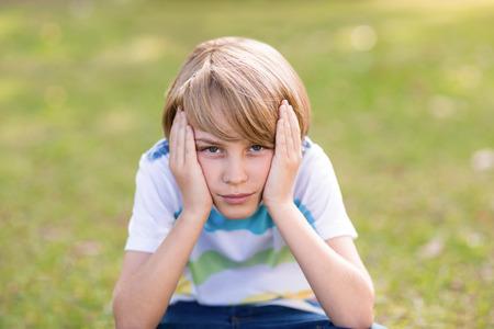 desolaci�n: Little boy feeling sad in the park on a sunny day Foto de archivo