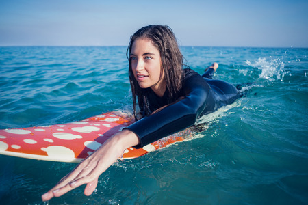 wetsuit: woman in wetsuit with a surfboard on a sunny day at the beach Stock Photo