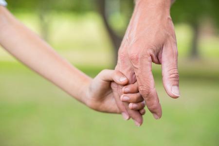 manos entrelazadas: Padre e hijo de la mano en el parque en un d�a soleado