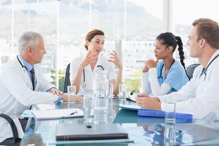 doctoras: Equipo de m�dicos sonrientes que tienen una reuni�n en la sala de reuniones