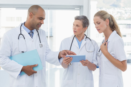 Team of smiling doctors working on their files in medical office Stockfoto