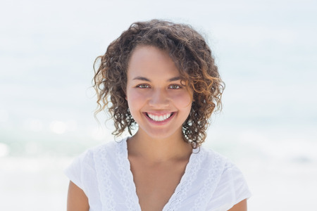 happy woman smiling at the beach 스톡 콘텐츠