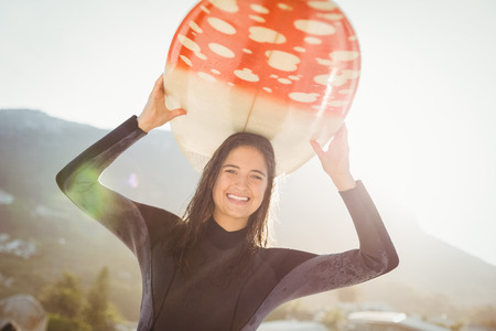escapism: woman in wetsuit with a surfboard on a sunny day at the beach Stock Photo
