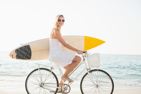 bike ride: beautiful blonde woman on a sunny day at the beach