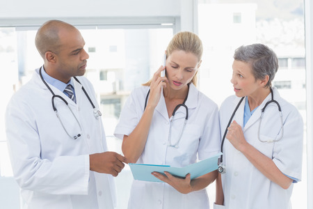 important phone call: Doctors having an important phone call in medical office Stock Photo