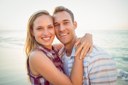 pareja abrazada: feliz pareja sonriendo a la playa
