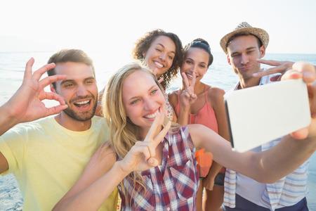 signo de paz: grupo de amigos que toman selfies en la playa