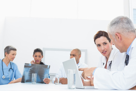 Team Of Doctors Working On Laptop In Medical Office Stock Photo ...