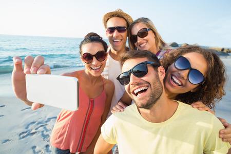 uomo felice: gruppo di amici che hanno divertimento in spiaggia