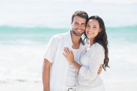 persona alegre: feliz pareja sonriendo a la playa