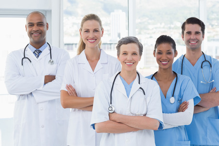 doctors smiling: Team of smiling doctors looking at camera in medical office