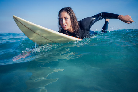 woman in wetsuit with a surfboard on a sunny day at the beach Stock Photo
