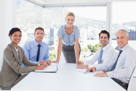 mature business man: Business team smiling at camera in the office Stock Photo