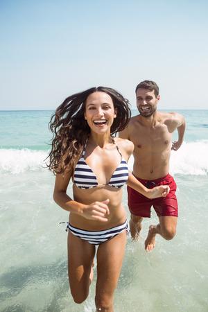 summer vacation bikini: happy couple smiling at the beach