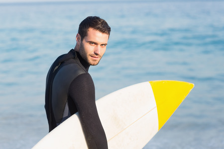 escapism: Man in wetsuit with a surfboard on a sunny day at the beach