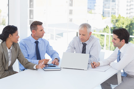 mature business man: Smiling businesswoman and her team in the office Stock Photo