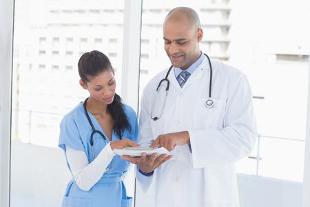 medical doctors: Smiling doctors reading files in medical office