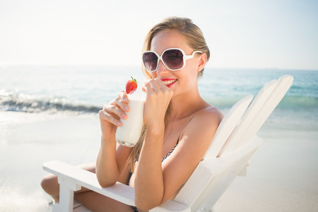 tomando alcohol: hermosa mujer rubia en un d�a soleado en la playa