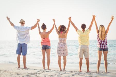 manos entrelazadas: grupo de amigos que se divierten en la playa
