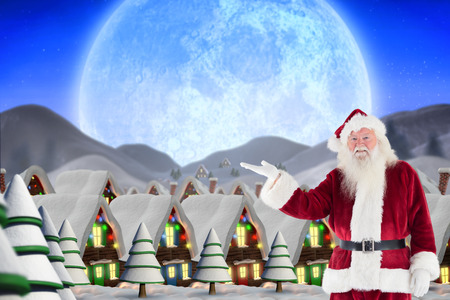 quaint: Santa shows something to camera against quaint town with bright moon