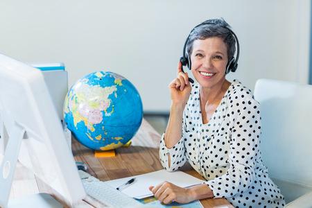Glimlachen reisagent vergadering op haar bureau in het kantoor