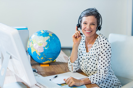 travel destinations: Smiling travel agent sitting at her desk in the office