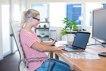 digitizer: Cheerful casual businesswoman using laptop and digitizer in the office