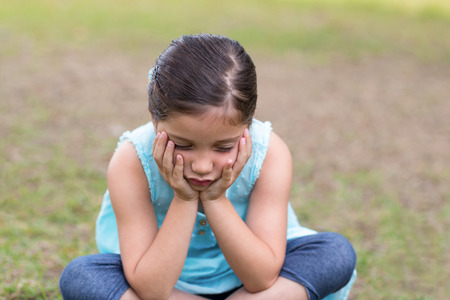 bleakness: Little boy feeling sad in the park on a sunny day Stock Photo