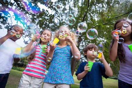 blowing: Little friends blowing bubbles in park on a sunny day