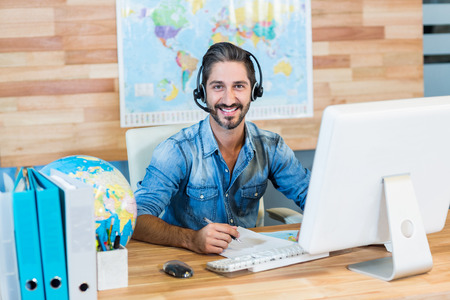 travel agent: Smiling travel agent looking at camera in the office