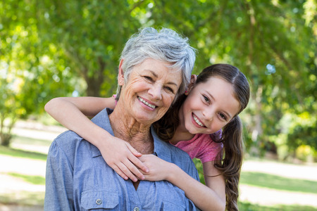 nieta y abuela sonriente en un parque en un día soleado Foto de archivo
