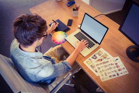 empresas: Feliz diseñador que trabaja en su computadora portátil en la oficina creativa Foto de archivo