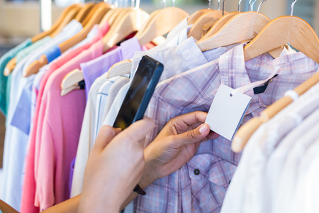 scanning: Woman scanning bar code with her mobile phone in clothes store Stock Photo