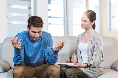 Psychologist talking with depressed man in the office Stock Photo