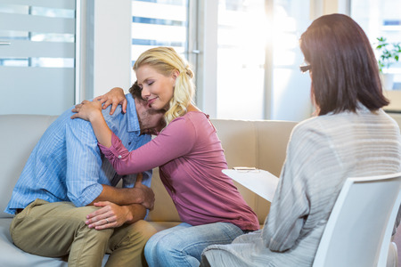 Reconciled couple hugging in the therapist office Stock Photo