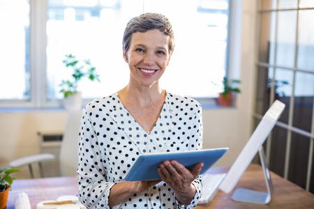 Lachende vrouw met tablet en kijken naar de camera in het kantoor Stockfoto