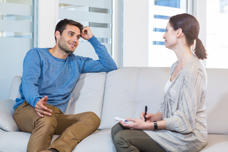 Psychologist talking with happy man in the office Standard-Bild