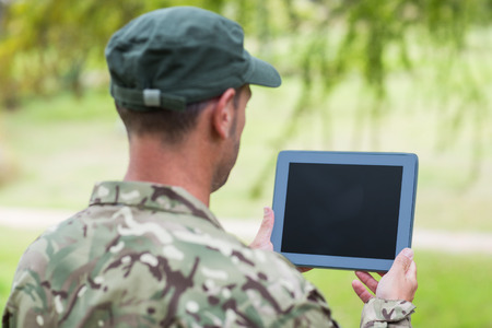 army soldier: Soldier looking at tablet pc in park on a sunny day Stock Photo