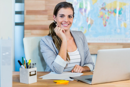 travel agent: Pretty travel agent smiling at camera in the office